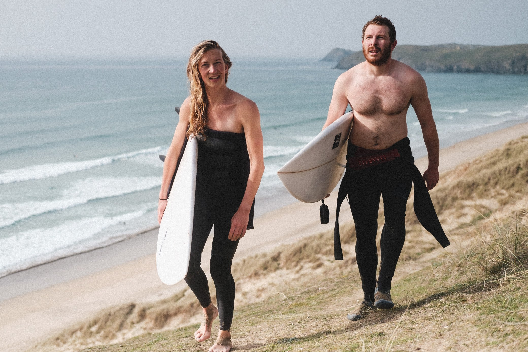 Surfer Couple walking up the sand dunes