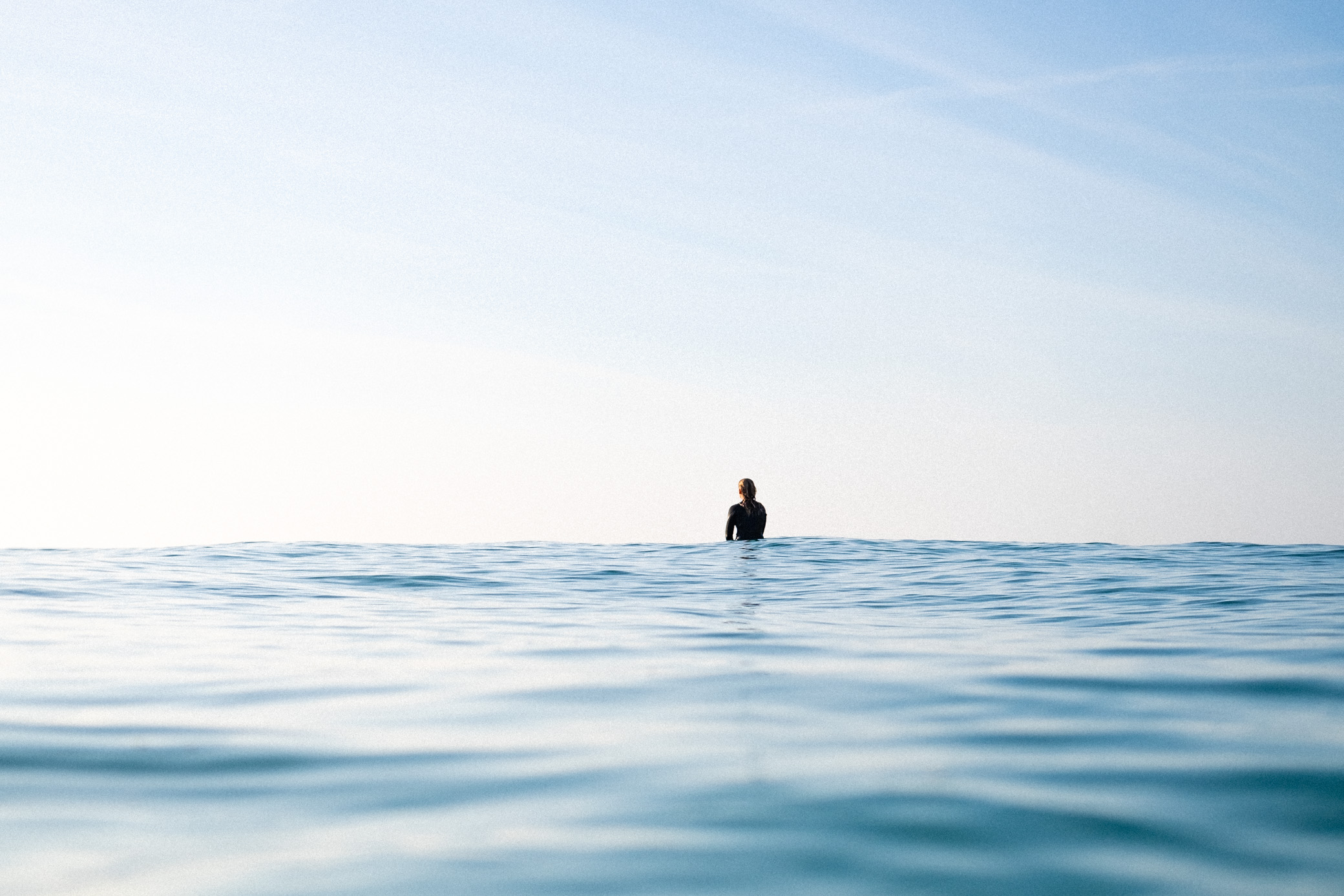 Waiting for waves, lone surfer girl sat in the sea